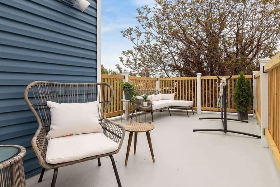 Concrete roof deck with white patio furniture by Bellweather Design-Build in Philadelphia