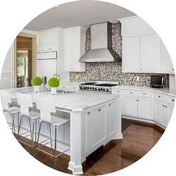 kitchen with beige patterned textured backsplash tile and white granite island with white barstool chairs