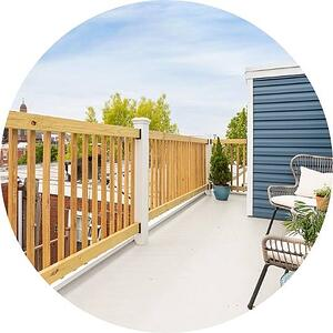 Rooftop deck with wood railing and white chairs by Bellweather Design Build in Philadelphia