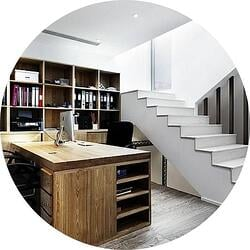 basement home office with white stairs and brown wood desk with mac computer
