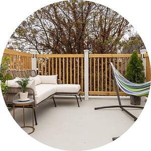 beautifully renovated rooftop deck with light brown wood railing and white chair and hammock by bellweather design build  in philadelphia