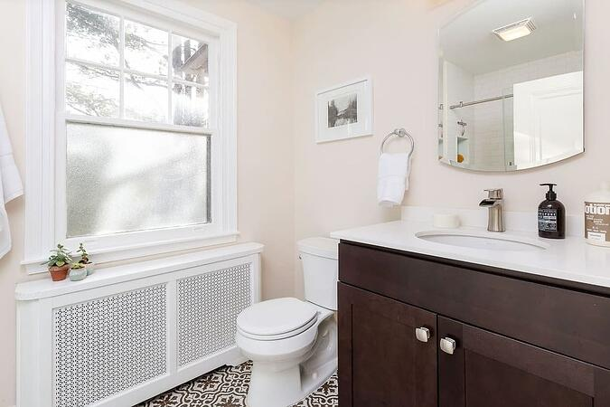 large midrange guest bathroom remodel with cream bathroom walls and white tiled shower by Belweather design build in Philadelphia