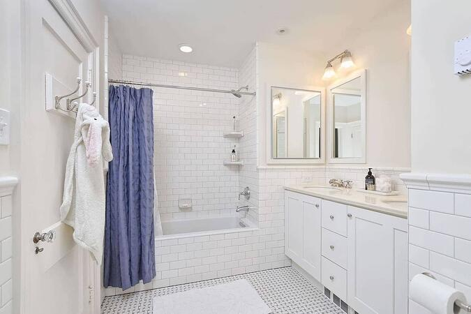 midrange bath remodel in philadelphia with white subway tile and blue curtain by Bellweather design build